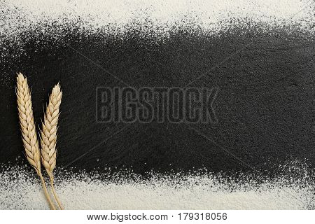 wheat ears and flour on black stone with blank space