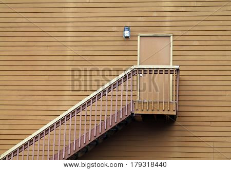 Wooden Stairs Leading to a Door in the middle of a Wall