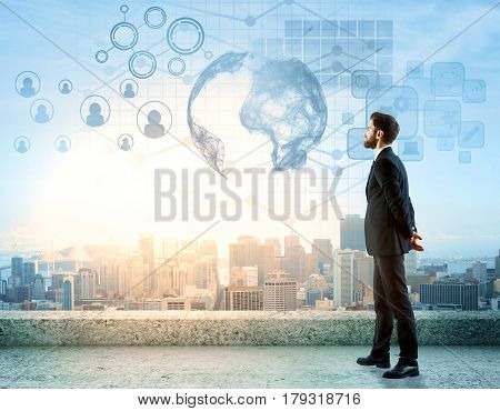 Side view of handsome young man standing on rooftop with digital charts globe HR and other icons. City view background. International business concept