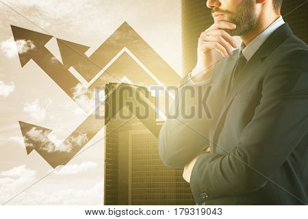 Side portrait of bearded young businessman with upward arrows on city background with sunlight. Financial growth concept