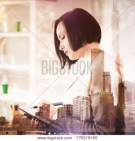 Side view of woman writing in notepad on abstract city background. Paperwork concept. Double exposure