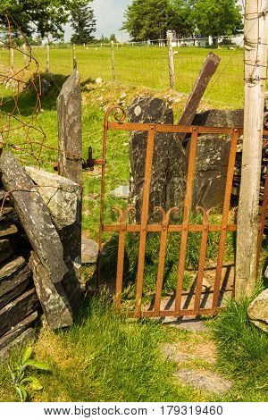 Rusting iron gate as stile in dry stone wall. North Wales United Kingdom.