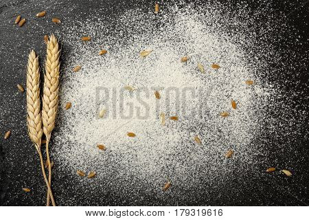 wheat ears and flour on black stone