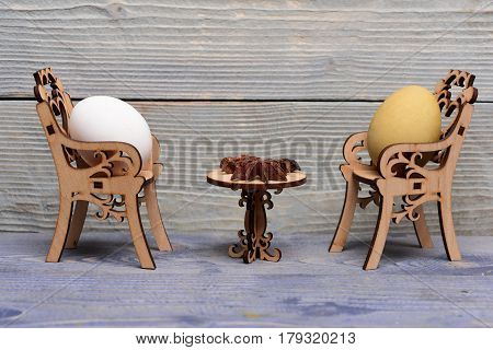 easter egg in wooden chairs at table with badian or star anise spice in dining room on grey wood background spring holiday celebration