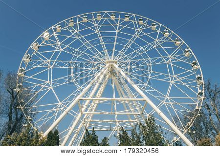 White ferris wheel against a blue sky.