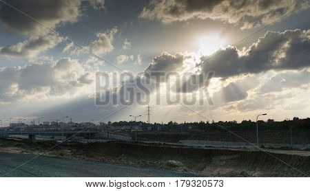 Wide angle shot of dramatic sunset with flare and godrays near Herzliya Pituah district with distant residential houses and bridge, clear sky and spindrift clouds, Israel in autumn.