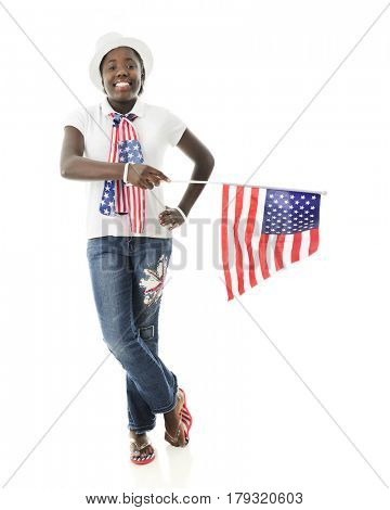 An attractive preteen girl proudly wearing her stars and stripes while holding the American flag.  On a white background.