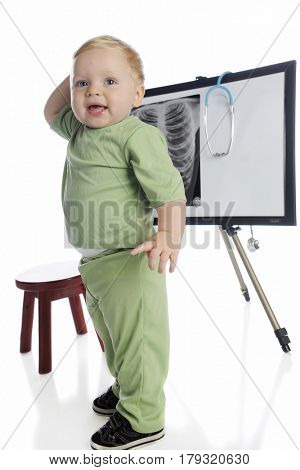 An adorable toddler playing x-ray technician in front of a chest x-ray on an ease[.  On a white background.