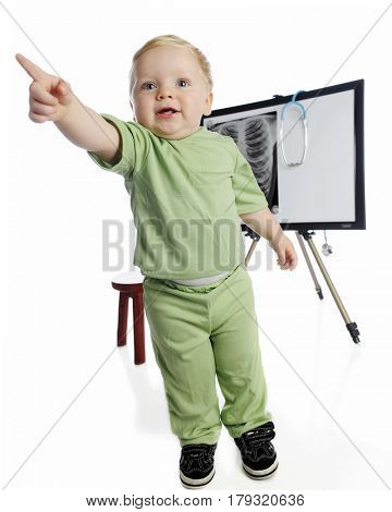 An adorable toddler boy playing x-ray technician. He's standing, pointing away from the x-ray on an easel behind him.  On a white background.