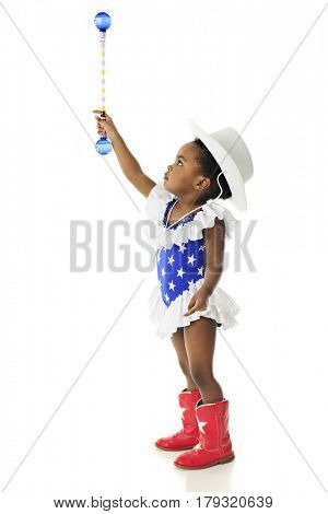 Profile of an adorable two year old in an American patriot outfit reaching high with her baton.  On a white background.