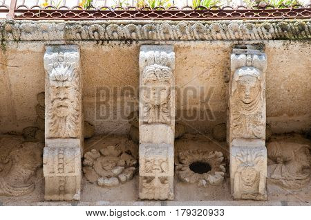 View of some stone mascarons under the balcony of a baroque palace in Caltagirone Sicily