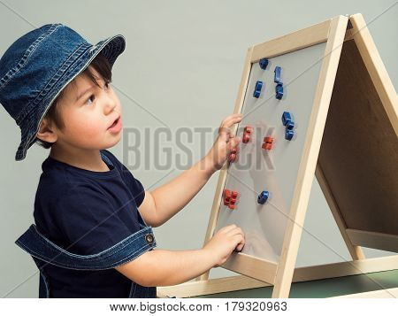 A little boy arranges letters and numbers on a magnetic board