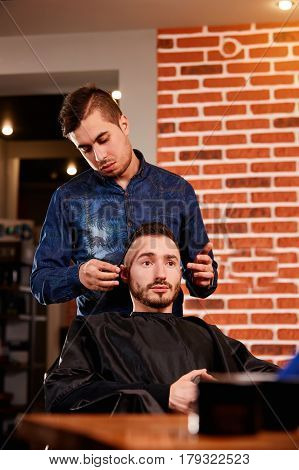 Master combing hair of men in the barbershop, hairdresser makes hairstyle for a young man. Beautiful. Pofessional and craftmanship. Two man in the barbershop. Background of the brick wall.