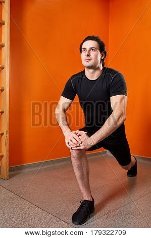 beautifull strong athletic guy, execute exercise in sport-hall in the gym. Sportsman in the black sportwear, t-shirt and shorts, black sneakers. Background of the bright orange wall. Squatting. Knee. Healthy lifestyle.