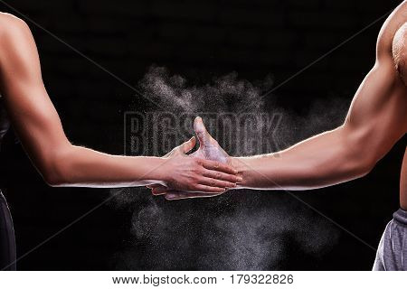 Cropped image of hands of a young couple on dark background. Crossfit fitness sport training lifestyle bodybuilding concept. Healthy lifestyle. Muscles. Bodypart. Detail.