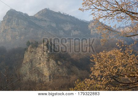 Rocks in the mountains of the Caucasus in a hazy haze with autumn, golden leaves on the trees in the foreground