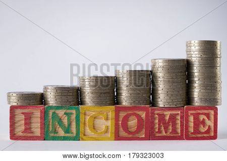 INCOME text written on wooden blocks with stacked silver coins isolated on white background.Income increase concept with upward pile of coins.