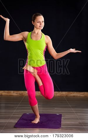 Beautiful young woman working out indoors, doing yoga exercise on violet mat, standing in Vrksasana Posture, Tree Pose. Woman in the sportwear, pink leggings and green t-shirt. Healthy lifestyle.