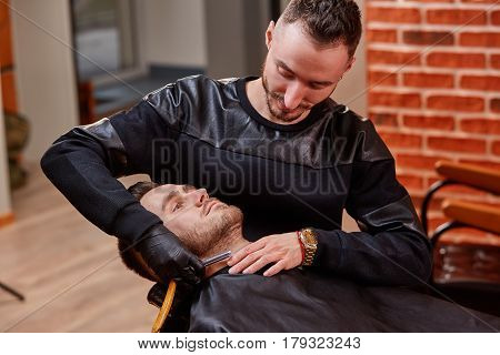 Handsome bearded man is getting shaved by hairdresser at the barbershop. BAckground with brick wall. Shaver. Two man. Professional and craftmanship. Style. Beautiful. Maste. Instrument.