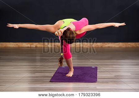 Beautiful healthy woman doing Triangle Utthita Trikonasana yoga pose standing on violet mat, with dark background. Woman in the sporty clothes, pink leggings and green t-shirt. Healthy lifestyle.