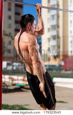 Young muscular build man doing pull ups exercises on horizontal bar outdoors, strong athletic man with naked abc training hard at sunny afternoon outside, sportsman working out. Healthy lifestyle. Photos from the back.