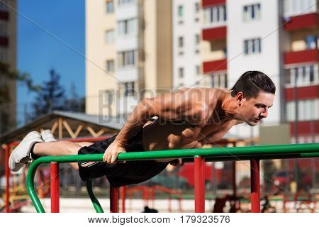 Fit man workout out arms on dips horizontal bars training triceps and biceps doing push ups outdoors. Horizontal push-ups. Outdoor in the city, Black short and white sneakers.