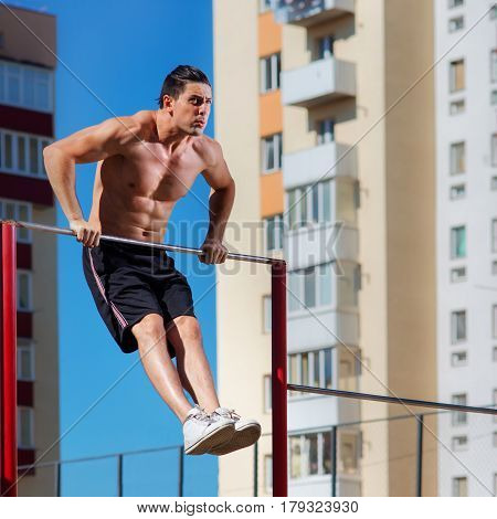Workout, sportsman pull ups the horizontal bar with big effort. Face with emotions. Sport activities on the outdoor. Background with blue sky. Abs. Healthy lifestyle. Sportsman in the black short and white sneakers.