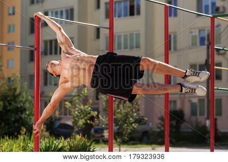 Fit man workout out arms on dips horizontal bars training triceps and biceps doing push ups outdoors. Man in the black short and white sneakers. Abs. Healthy lifestyle.