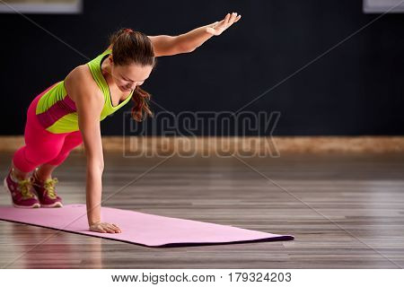 Beautiful sporty women practicing the yoga pose during a class in a gym. On the pink yoga mat. Woman in the sporty clothes, pink leggings and green t-shirt. Healthy lifestyle.