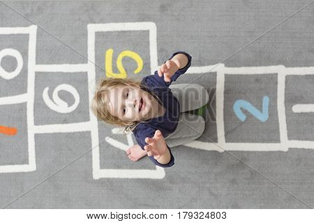 Little girl playing hopscotch