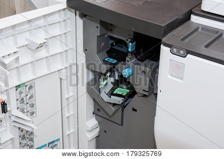 Closeup in front of open photocopier during maintenance repairs using black mechanical parts