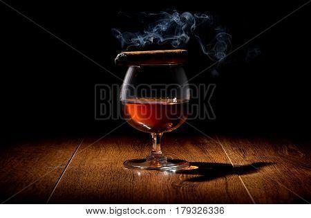 Havana cigar on a wineglass of whiskey
