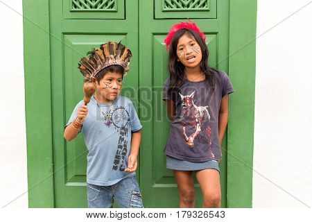 Paraty, Brazil - February 25. 2017: Brazilian Indian children in front of big green colonial door singing traditional Indigenous songs for tourists visiting the old town.