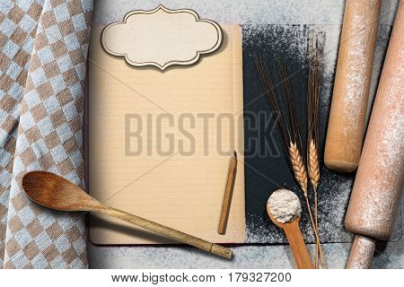 Empty recipe book with label and lined paper on a baking background with flour ears of wheat wooden kitchen utensils and a checkered tablecloth