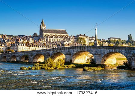 Old bridge over the Loire at sunset in Blois, France. Cathedral of Blois in the background.