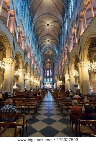 PARIS - SEPTEMBER 25, 2013: Tourists visiting the Notre Dame de Paris. The cathedral of Notre Dame is one of the top tourist destinations in Paris.