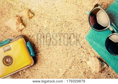 Waterproof camera and beach accessories on sand Summer concept with copy space. Sunny bright travel background