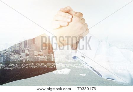 Close up of two businessmen shaking hands while standing against a cityscape. Double exposure.
