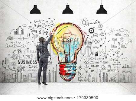 Rear view of a businessman drawing a large and colorful light bulb sketch surrounded by business icons on a concrete wall with three lamps hanging above him.