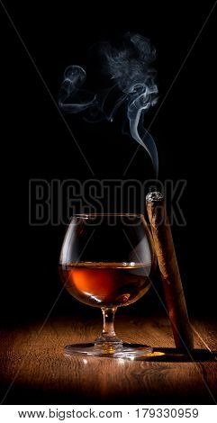 Wineglass of scotch and cigar on wooden table