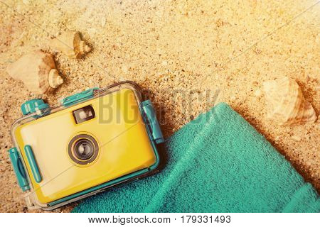 Travel camera and summer accessories on beach. Summertime concept with copy space. Sunny bright tourism background