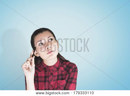 Portrait of a geeky young woman wearing a red checkered shirt and scratching her head with a pen while thinking and looking upwards. She is sitting against a blue background. Mock up