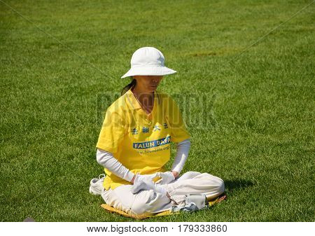 OTTAWA CANADA - AUGUST 19 2014: Woman practicing Falun Gong in OttawaCanada. Falun Gong or Falun Dafa is a Chinese spiritual practice that combines meditation and qigong exercises.