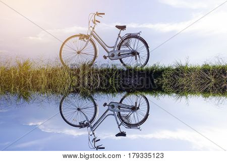 Reflection of Old vintage bicycle with dramatic blue sky at background