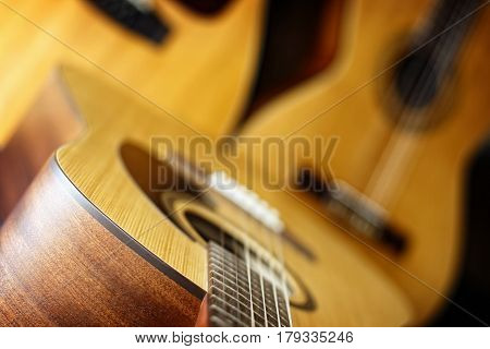 A trio of three acoustic guitars (standard six string in foreground classical six string and a twelve string in background) are combined to create a music themed image - shallow depth of field on foreground six string.