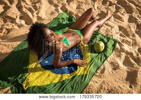 Young Beautiful Woman in Bikini Relaxing on Sand, Laying on the Brazilian Flag Beach Yoke With Coconut Drink Next to Her