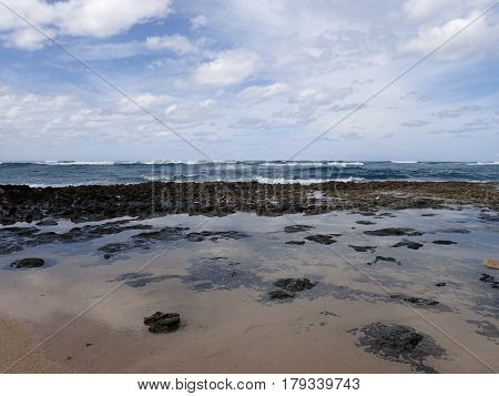 Lava Rocks and tide pools on Beach with waves from ocean moving towards shore at Turtle Bay Oahu Island North Shore Hawaii