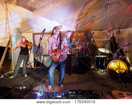 OAHU - FEBRUARY 20 2017: Rock band Roxotica featuring guitarist bassist violinist and drummer playing at Optimysstique 2017 Campout under a giant sail at Camp Mokuleia on the North Shore of Oahu