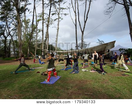 NORTH SHORE - FEBRUARY 19: Outdoor Yoga class led by Kara Miller does warrior two among large ironwood trees at Optimysstique Campout 2017. February 19 2017 Oahu Hawaii.