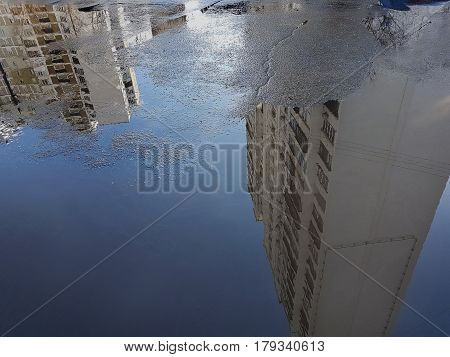 Puddle: On The Surface Of The Blue Water Are Reflected White Many Storey Buildings, On The Left Bott